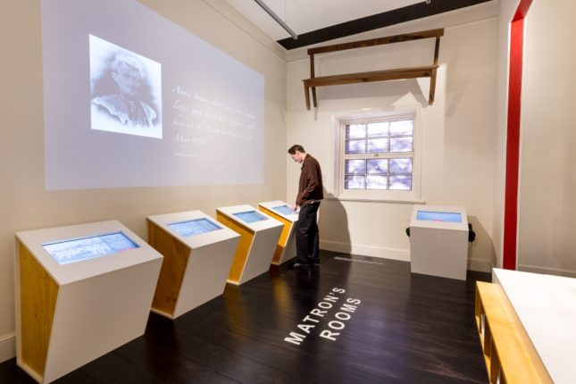 Person viewing In This Place exhibition at Migration Museum