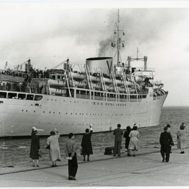 B&W photo of a migrant ship departing the dock