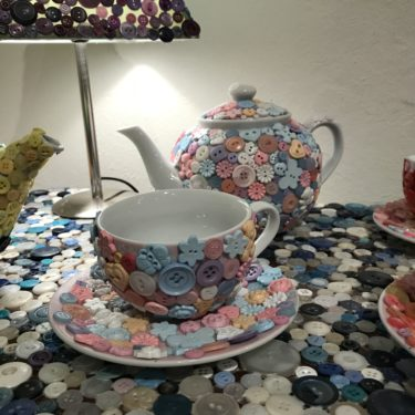 Close up image of artwork consisting of teapot and cup decorated with colourful buttons.