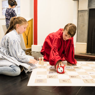 Two children playing an oversized board game in an exhibition gallery