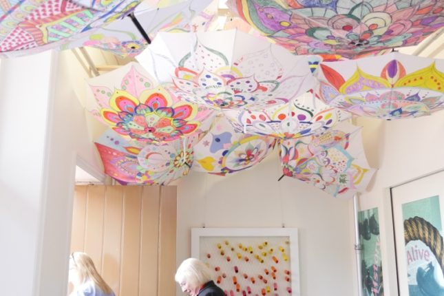 Colourful display of hand-decorated umbrellas hanging from the ceiling