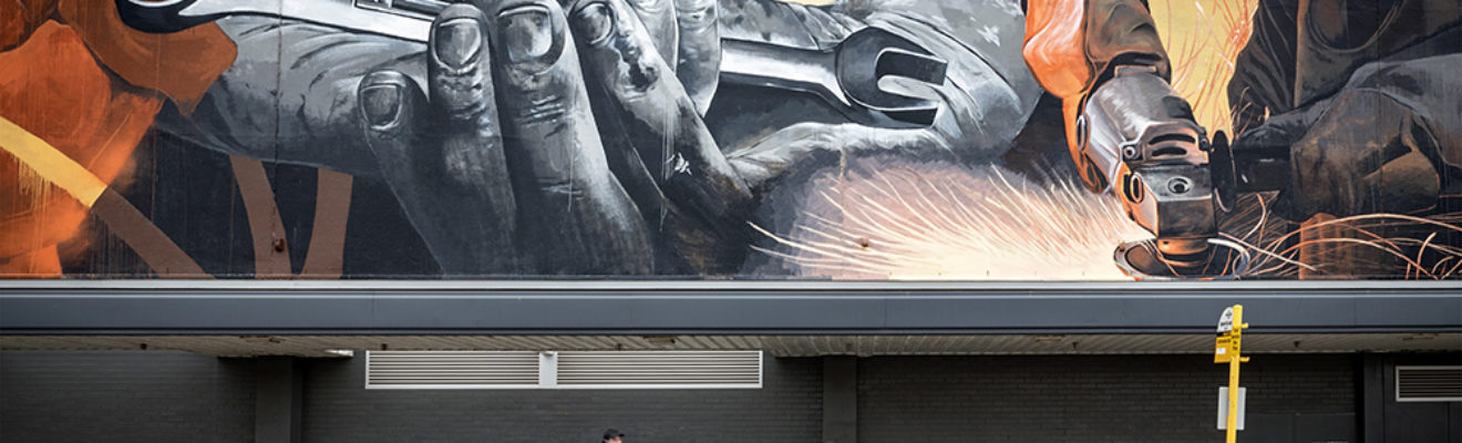 A man walks past a large mural that depicts metalwork in a car workshop