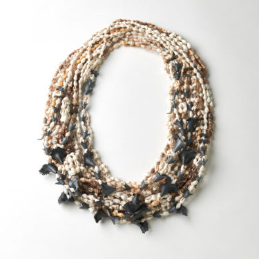 a large round necklace made of tiny shells